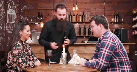 jeść : Bearded hipster waiter pouring wine from a bottle to his clients in a vintage rustic pub or restaurant