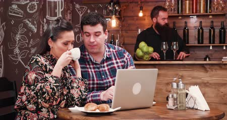 croissants : Couple drinking coffee and looking at computer screen in very cozy and stylish coffee shop, pub or restaurant with wooden walls. A bearded bartender is working in the background on the counter