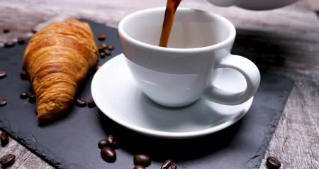 континентальный : Pouring a cup of coffee to serve with a tasty croissant. Coffee beans all arround. Beautiful composition.