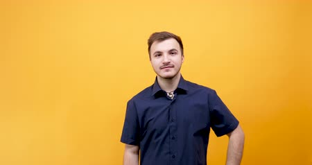 çılgın : Young happy man making silly faces isolated on yellow orange background in studio Stok Video