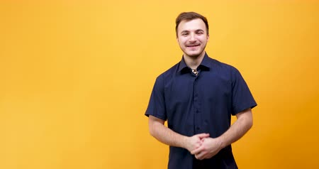 дружелюбный : Happy positive guy on yellow background in studio Стоковые видеозаписи