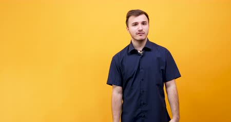curto : Young caucasian man making I don t know gestures to the camera isolated on yellow orange background