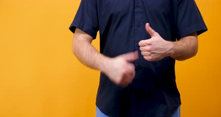 emelt : Close up of male hands showing thumbs up to the camera on yellow orange background Stock mozgókép