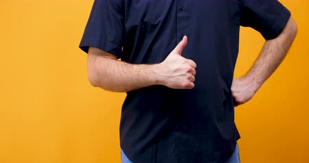 emelt : Caucasian male hands showing thumbs up to the camera. Isolated on yellow orange background in studio