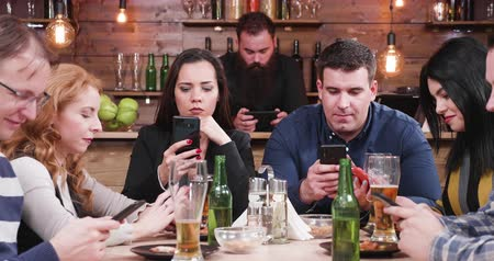 sem problemas : Friends in pub all looking at smartphone instead of talking to each other and spending time together. Modern society problem Stock Footage
