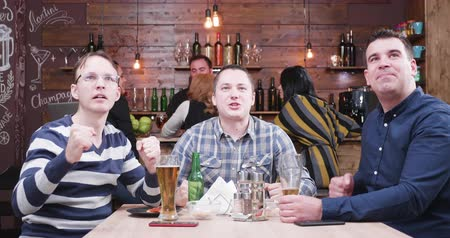 фэн : Zoom in shot of group of male friends watching a football game in vintage pub or restaurant. They are cheering when their favourite team scores