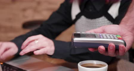 lezer : Close up shot of woman paying for coffee with her smartphone using NFC payments. Financial technology