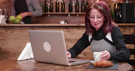 кошелек : Adult businesswoman pays for coffee using a contactless credit card. She is working on the computer in a vintage coffee shop