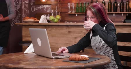 перевод : In stylish coffee shop adult businesswoman pays for her coffee using a contactless credit card