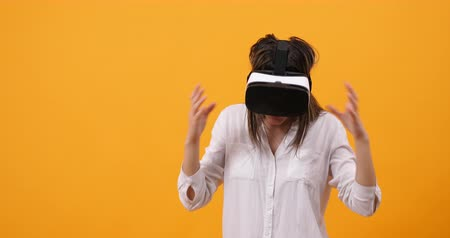 vr headset : Amazed woman making gestures while enjoying VR experience for the first time. Isolated over yellow background