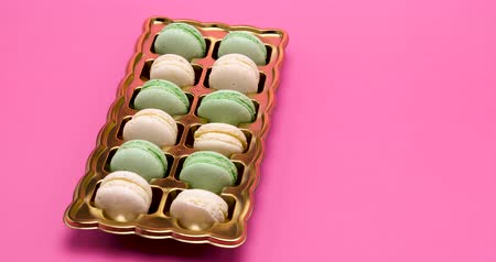 macarons : Macaroon dessert in a special box in rows on pink background in studio Stock Footage