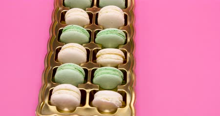 konfekció : Sweet delicious macaroons in a box on pink background in the studio
