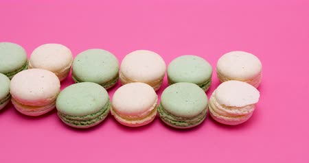 macarons : Row of fresh and delicious macaroons dessert on pink background in studio Stock Footage