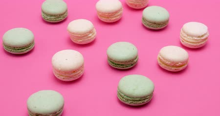 şekerleme : Sweet tasty macaroons on pink background in studio Stok Video