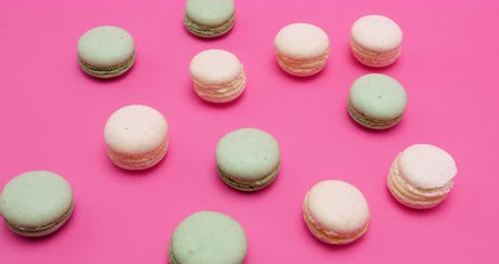 macarons : Macaroons in different colors on pink background in studio Stock Footage