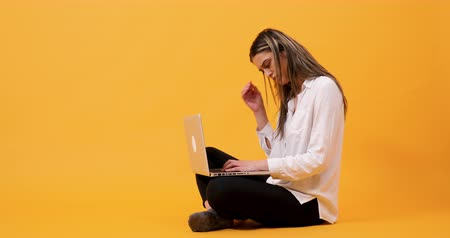 yazılım : Young woman typing fast and having an ideea. Shot on yellow background in studio