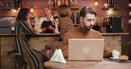 kafeterya : Young freelancer lured by a cup of coffee when working in a crowded coffee shop. Costumers are having fun at the bar. Stok Video