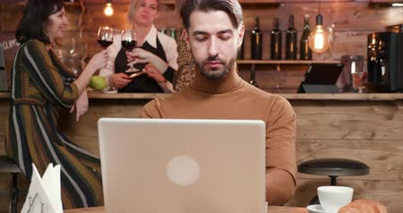 káva : Young man with a laptop working and enjoying his coffee. In a coffe shop while people drink wine at the bar