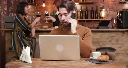 kafeterya : A handsome young businessman talking on his phone while working in a bar. A young freelancer managing his business from a restaurant Stok Video