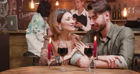 restoran : A young couple spending the night in a restaurant, enjoying each others company on a romantic date. drinking wine