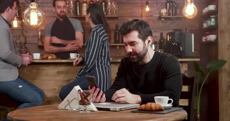 kruvasan : Young handsome man engaged in a video call while serving his coffee in a cafe. Having a friendly video chat while freelancing in a coffee shop.