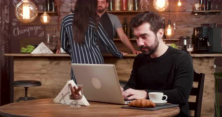 kafeterya : A caucasian man with beard works at his laptop while customers enter the coffee shop. Enthusiastic young businessman works on an online job.
