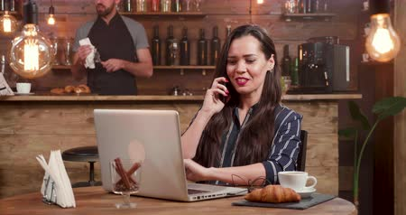 antwoorden : Pretty, brunette woman answers a phone call while working on her laptop remotly. Working as a freelancer from a coffee shop. Stockvideo