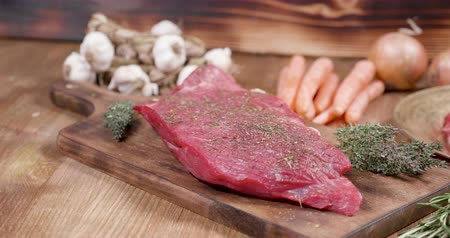 beef dishes : Panning over seasoned raw meat. Meat on vintage wooden boar and beautiful retro background. Beautiful composition of raw meat with vegetables and spices. Stock Footage