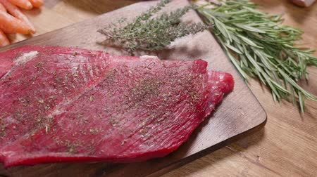 tomilho : Slowly revealing a fresh raw chunk of meat on an aged wooden board. Wooden background decorated with thyme and rosemary.