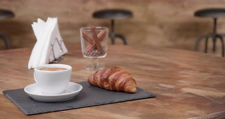 aromatik : Revealing shot of a fresh cup of black coffe with a delicious croissant. Wooden table and wooden bar counter on the background.