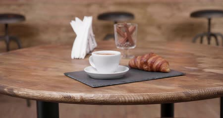 aromatik : Slowly moving towards a restaurant table with an espresso and croissant on it. Minimalist composition in a wooden vintage style coffee shop.