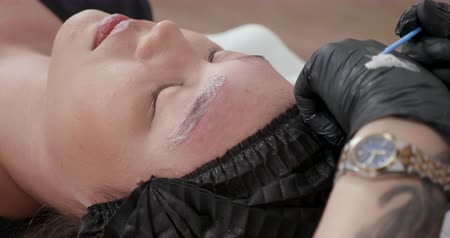 permanente : Applying the Glycolic Acid on the eyebrows to pull the ink out of the tattooed skin. Woman having her eyebrow tattoos removed in a beauty salon. Filmati Stock