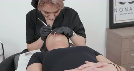 kap : Beautician dressed in black performing a microblading technique. A woman gets a beauty facial procedure for her eyebrows.