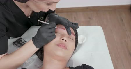 brow : Top view, slide shot from right to left at a cosmetologist visit. Beauty salon during a beauty procedure. Stock Footage