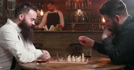 bourbon whisky : Two friends with stylish beards playing a chess game in a pub. Men with long beards playing chess game and enjoying whiskey in a elegunt bar.