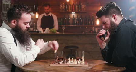 бурбон : Two bearded friends drinking and smoking while playing chess in a pub. A man inhales the smoke from his electronic cigarette and another man drinks bourbon Стоковые видеозаписи