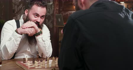 bourbon whisky : Young handsome bearded man playing chess with his friend in a pub. Confident and serious guys playing a chess match. Stock mozgókép