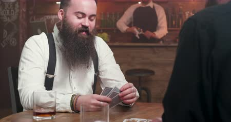 bourbon whisky : Man with long beard smiling and playing cards with a friend