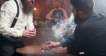 виски : Two friends in a bar having glass of whiskey and smoking heavily Стоковые видеозаписи