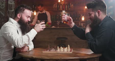 não alcoólica : Two stylish men having a conversation over a glass of whiskey and a chess game