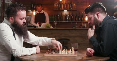 bourbon whisky : Male friends with beards met in a bar to play a chess game Stock mozgókép