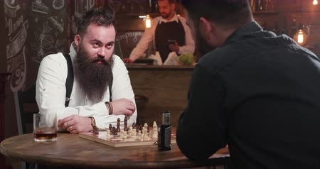 bourbon whisky : Confident chess player with beard over a game in a bar