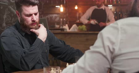 bourbon whisky : Man with beard looking at the chess board and drinking whiskey Stock mozgókép