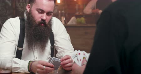 бурбон : Revealing shot of a young man with big beard playing a card game with a rival Стоковые видеозаписи