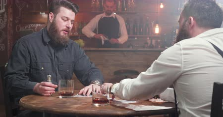 bourbon whisky : Two best friends dealing playing cards and starting a game Stock mozgókép