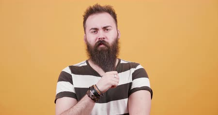 sincerely : Pretty young bearded man dressed in a t-shirt in front of yellow background. Medium close-up shot of a young hipster caressing his big beard.