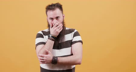 orange t shirt : Man with long beard showing signs of worry and concern