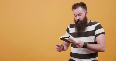 orange t shirt : Young bearded man reading a book to an audience Stock Footage