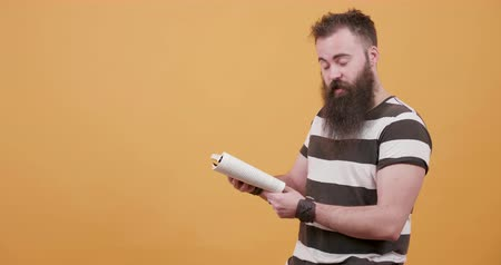 orange t shirt : Young handsome bearded man reading a book out loud