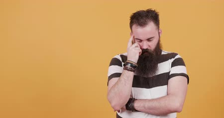 orange t shirt : Bearded young hipster thinking of an ingenious idea and the bulb lights up Stock Footage